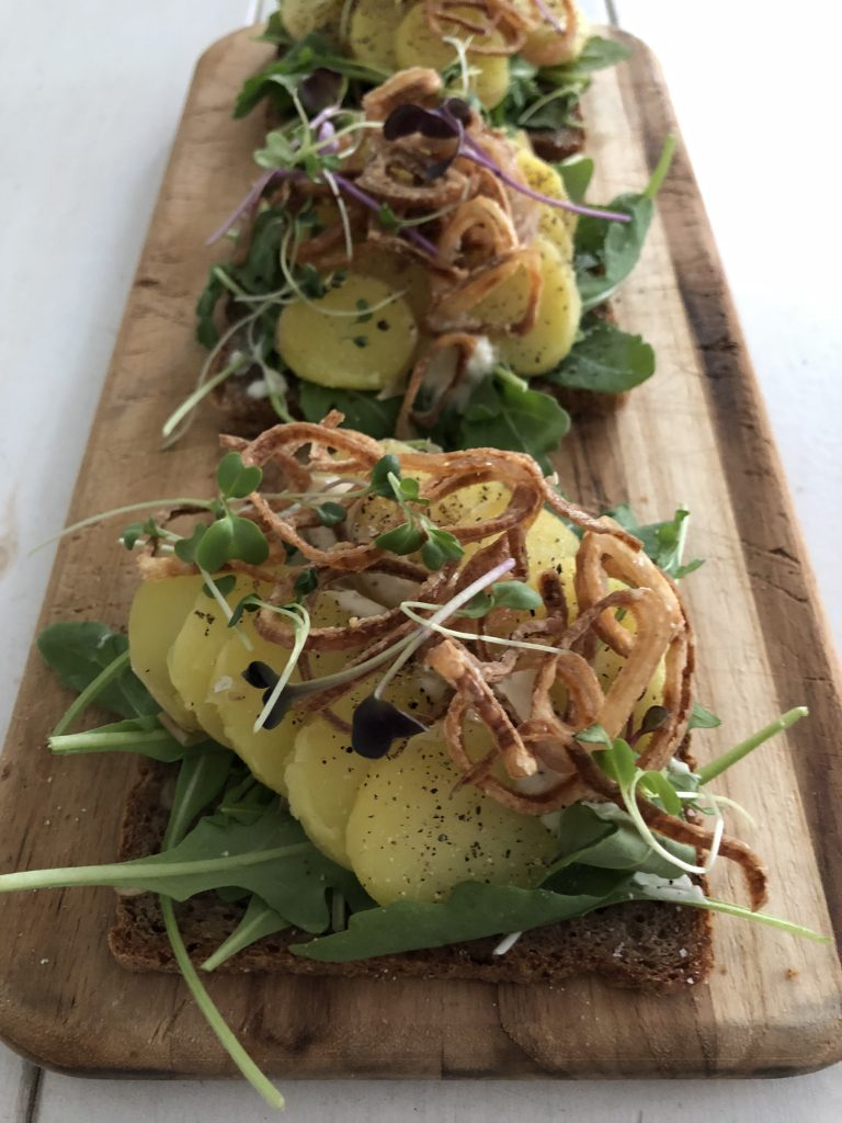 An open sandwich with lettuce, potatoes, and crispy shallots on a cutting board