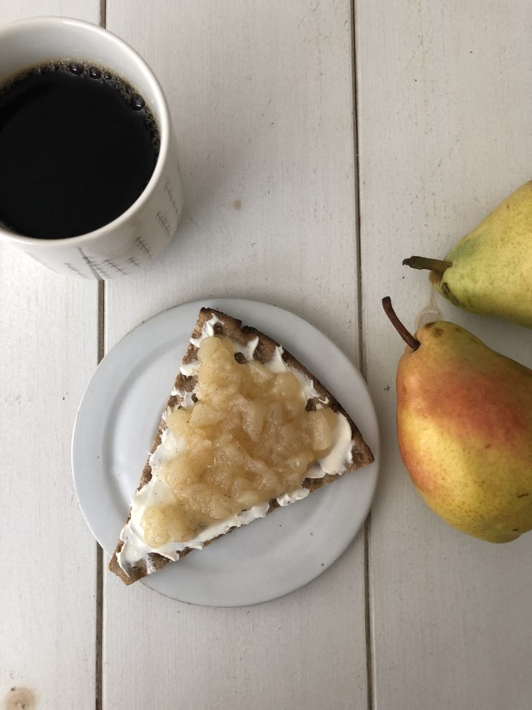 Crispbread topped with cream cheese and pear compote on a plate next to fresh pears and a cup of coffee