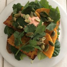 Open sandwich topped with lettuce, roasted squash, creamy sauce and pepitas on a plate