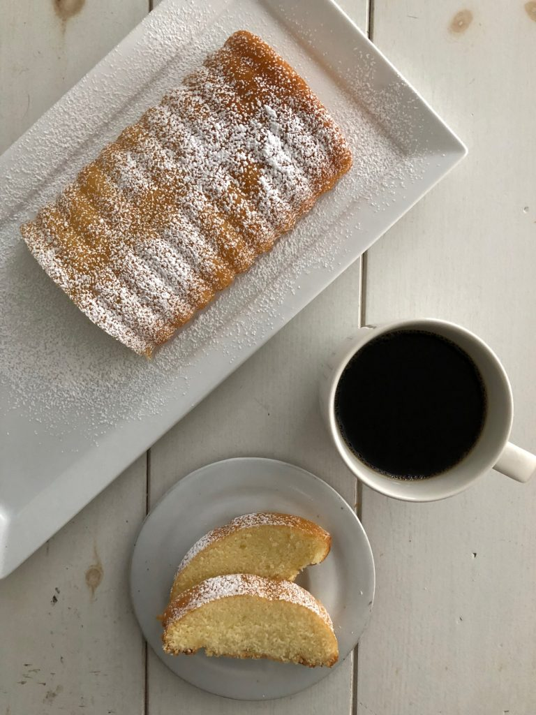 Swedish almond cake on a platter next to a cup of coffee and two slices of cake stacked on a plate
