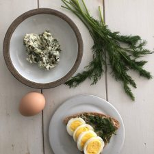 A bowl of herb butter next to a sandwich on a plate, an egg and fresh dill
