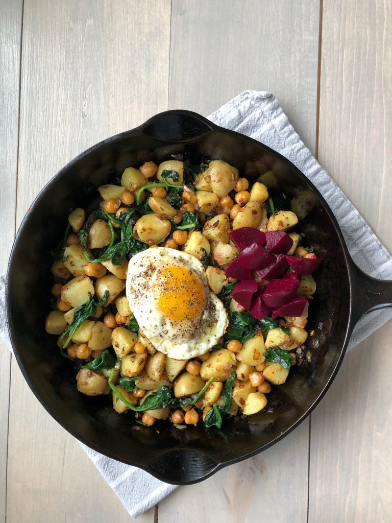 A skillet filled with pytt i panna, a fried egg and pickled beets on a kitchen towel