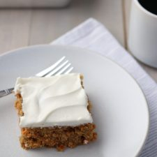 A piece of carrot cake on a plate with a fork, napkin and cup of coffee