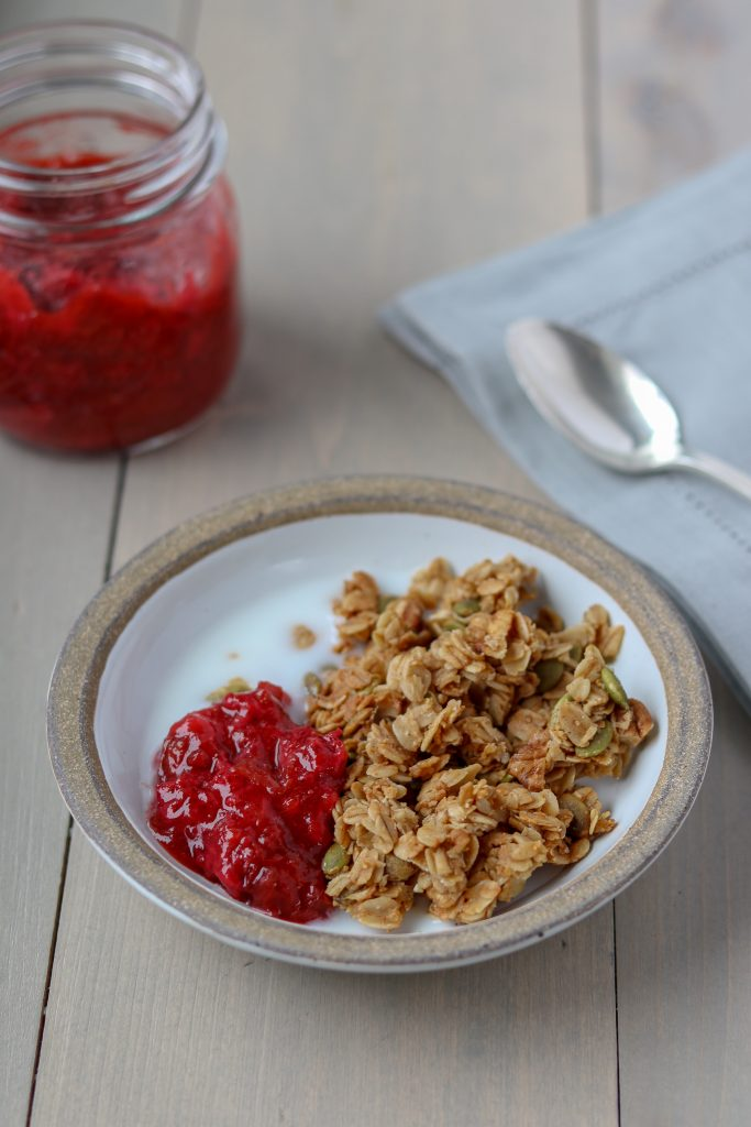 Granola, milk and strawberry rhubarb compote in a bowl next to a spoon and napkin