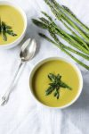Two bowls of asparagus soup topped with asparagus next to a spoon and fresh asparagus