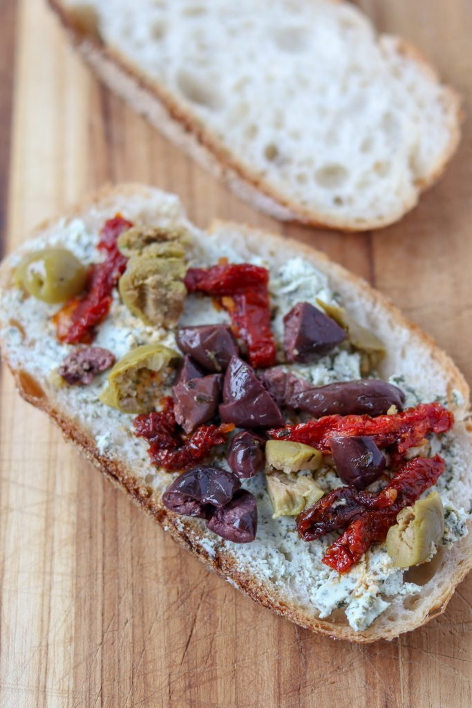 A slice of bread topped with goat cheese, olives and sun-dried tomatoes sitting on a cutting board