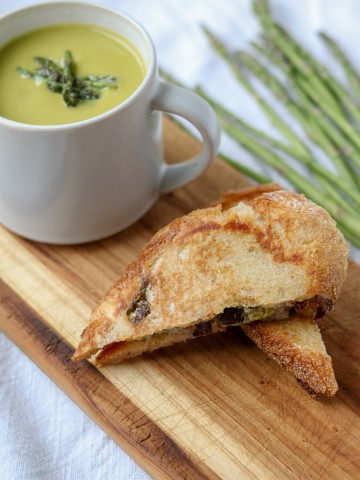 A mug of asparagus soup next to a grilled cheese sandwich on a cutting board