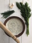 Creamy skyr sauce in a bowl with a wooden pestle and fresh herbs