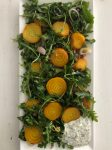 Arugula salad topped with golden beets and shallots on a platter