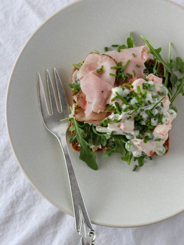 An open ham sandwich on a plate with a fork