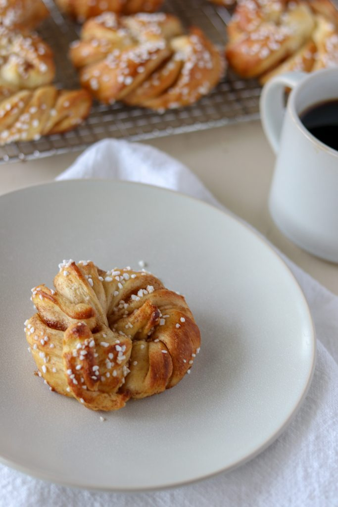 A Swedish cinnamon bun on a plate next to a cup of coffee