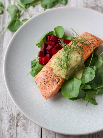 Salmon with mustard sauce, pickled beets and salad on a plate