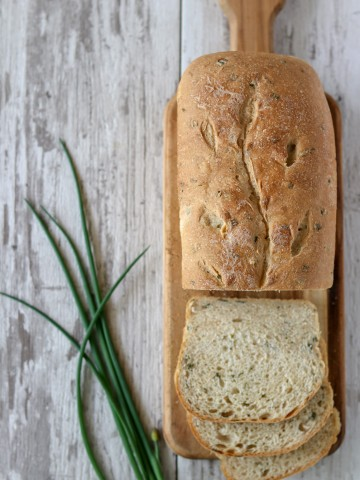 A loaf of chive ricotta bread on a cutting board next to fresh chives