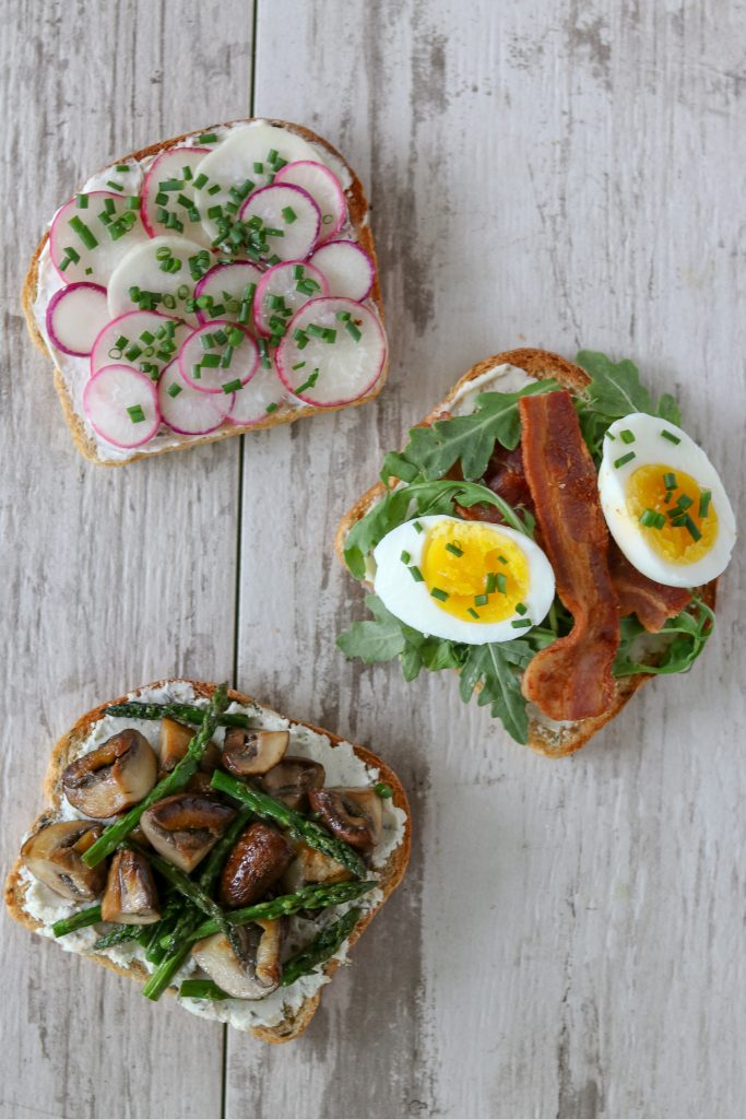 Three open sandwiches on a wooden surface