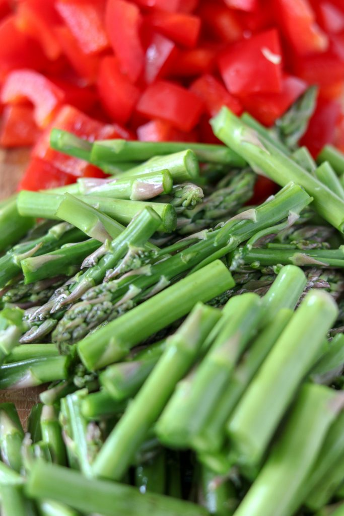 A close up of chopped asparagus and red pepper