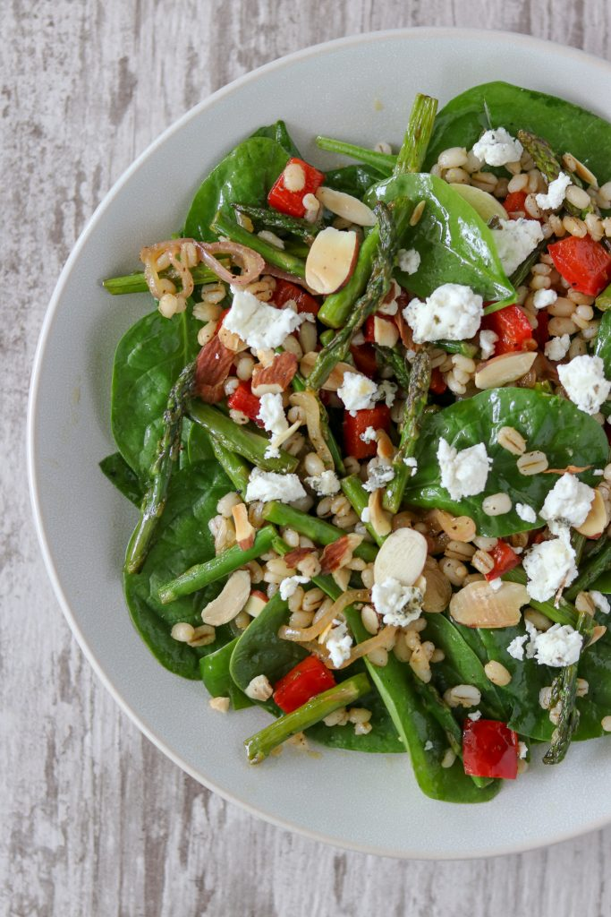 Asparagus, red pepper and spinach salad topped with goat cheese on a plate