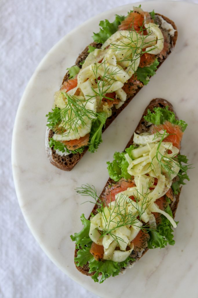 Open sandwiches topped with lettuce, salmon and fennel on a marble plate