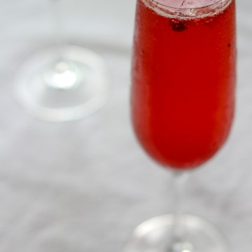 A close up of a Swedish 75 cocktail in a champagne glass