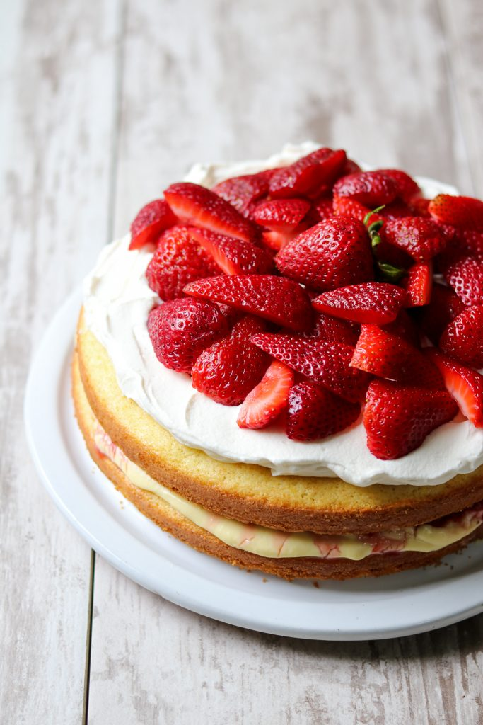 Strawberry cream cake topped with fresh strawberries on a plate