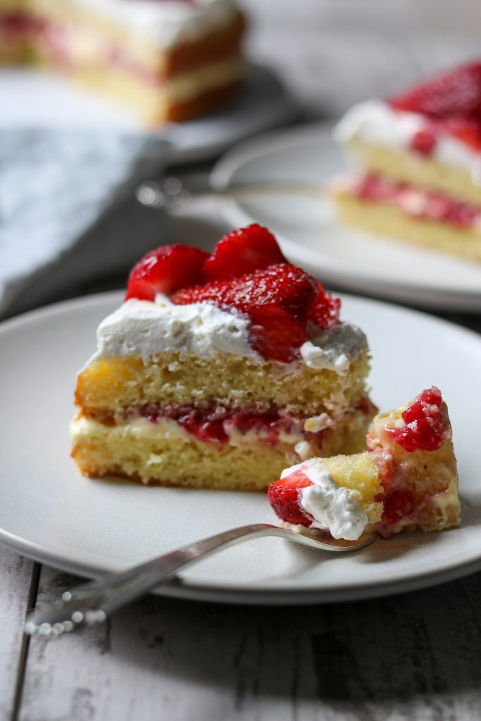 A close up of a piece of strawberry cream cake with a fork