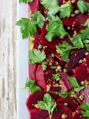 A close up pickled beet salad on a platter topped with parsley leaves