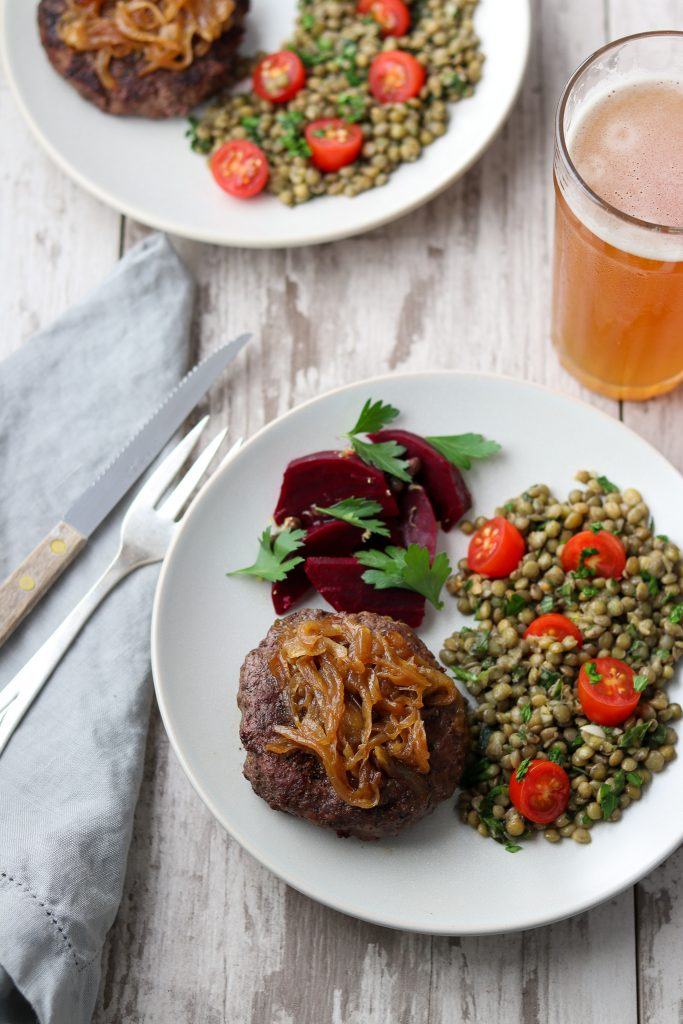 A hamburger, pickled beets and lentil salad on a plate next to a fork, knife, napkin and glass of beer