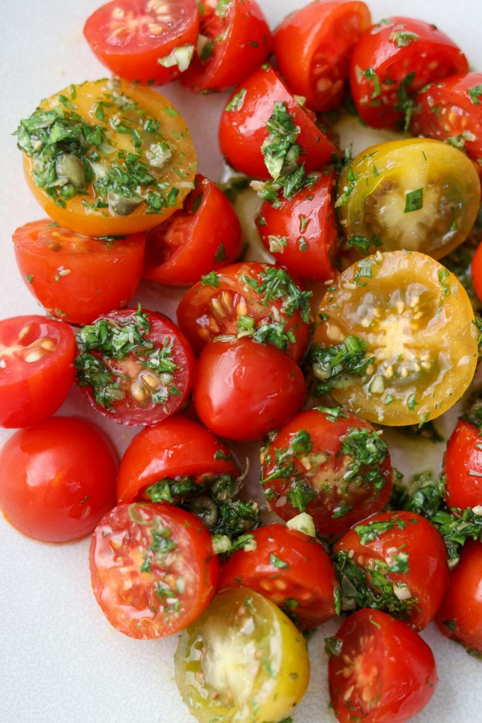 A close up of cherry tomatoes tossed with fresh herb sauce