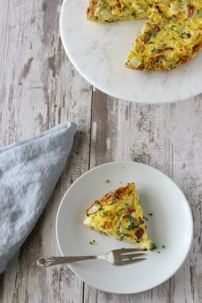 A slice of Danish egg cake on a plate next to a blue napkin