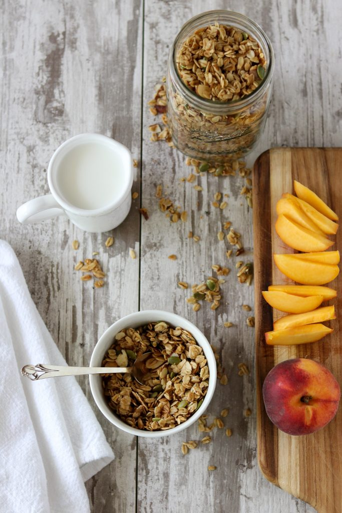 A bowl of granola with a spoon next to milk, a napkin and sliced peaches on a cutting board