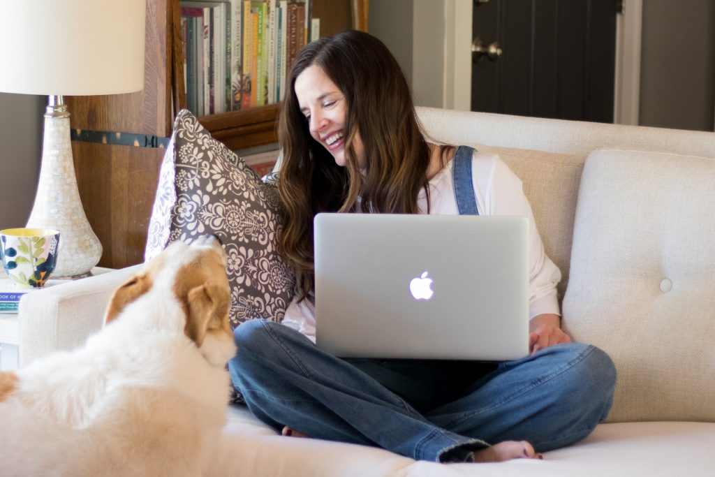 Kristi Bissell sitting on the couch working on her laptop with her dog