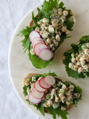 Open sandwiches with chickpea salad, radishes and lettuce on a plate