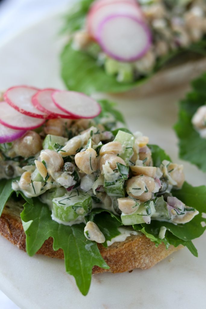A close up of an open face sandwich topped with lettuce, chickpea salad and radishes