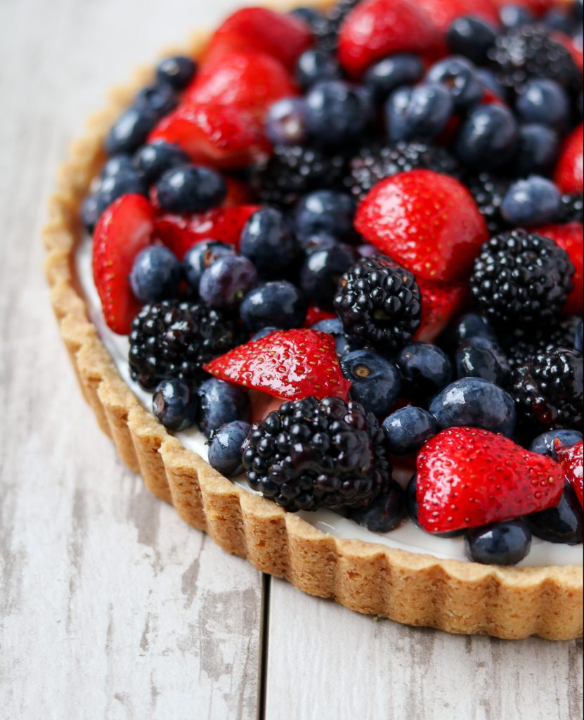 A close up of a skyr tart with fresh berries on a wooden surface