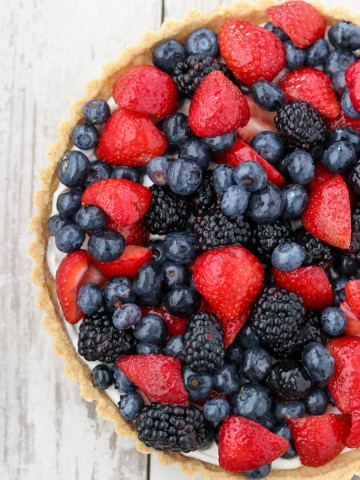 A skyr tart with fresh berries on a wooden surface