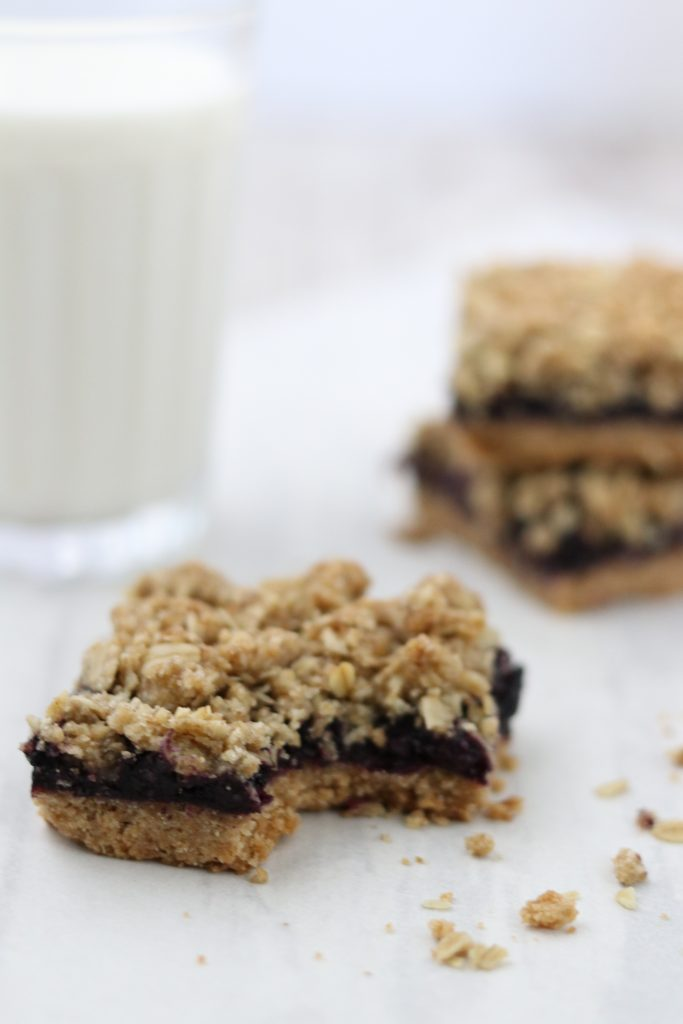 A close up of blueberry crumble bars with a glass of milk