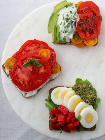 Open sandwiches with tomatoes and egg on a marble plate