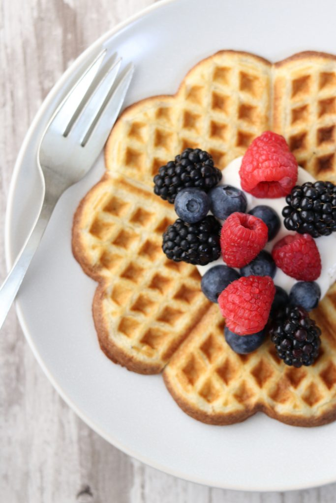 A waffle topped with whipped cream and berries on a plate next to a fork