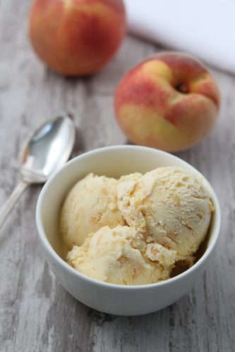 A bowl of roasted peach ginger ice cream next to a spoon and fresh peaches