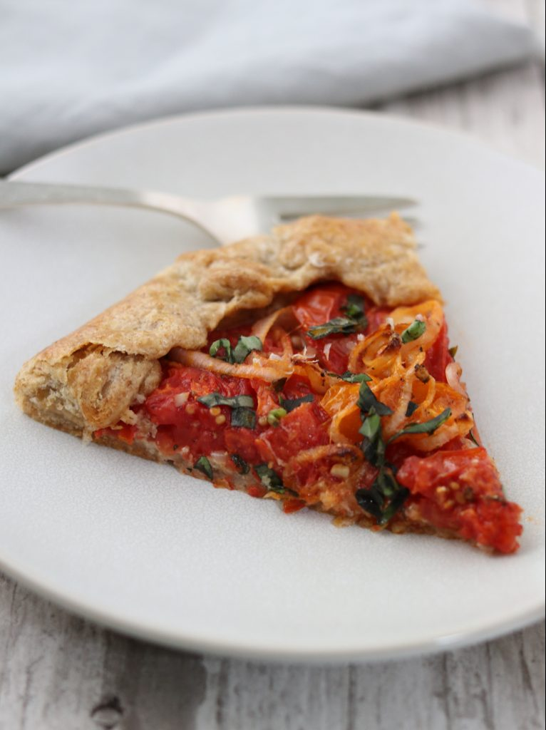A slice of tomato tart on a plate with a fork