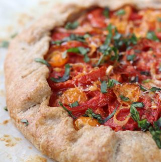 A close up of a rustic tomato tart topped with basil