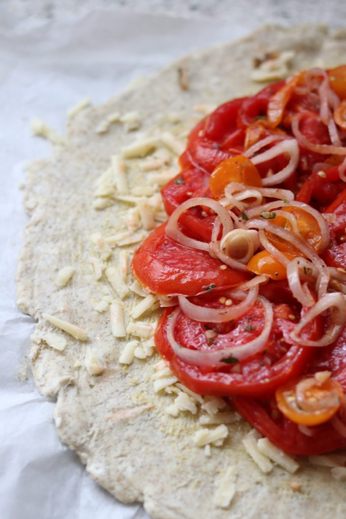Tart dough topped with cheese, sliced tomatoes and shallots