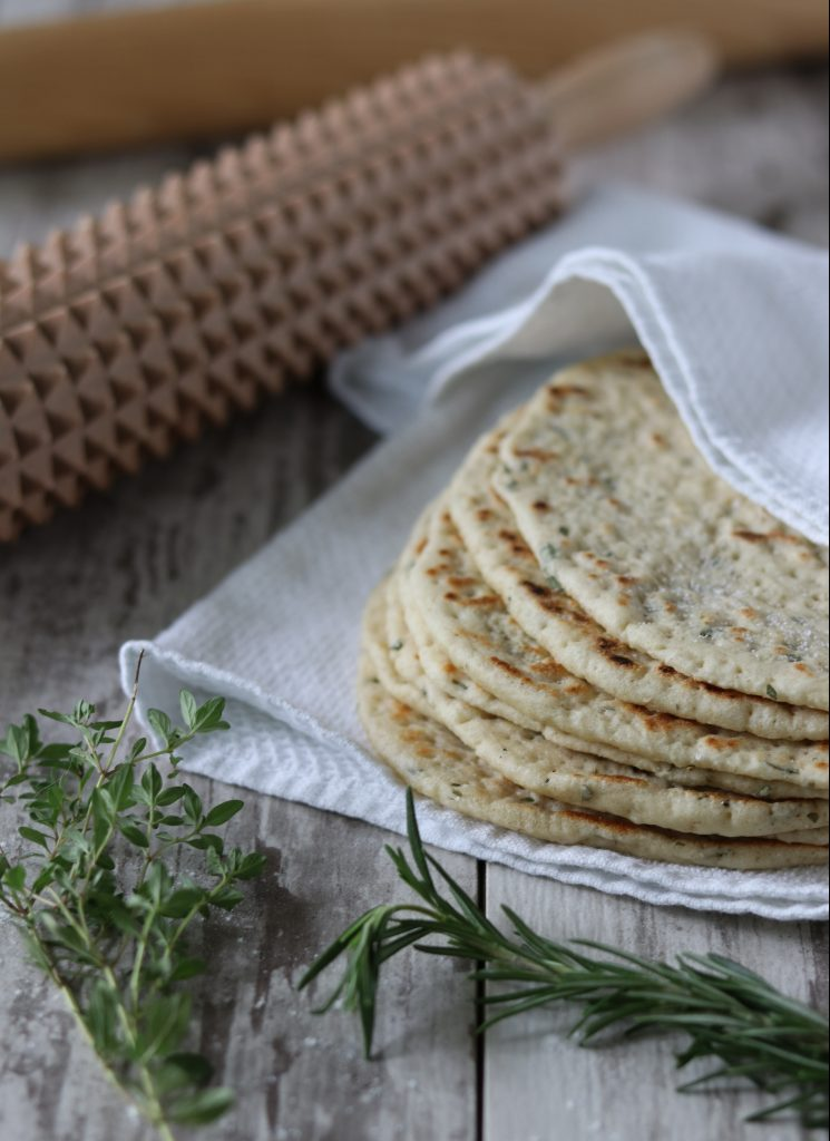 A stack of flatbreads on a towel next to a rolling pin and fresh herbs