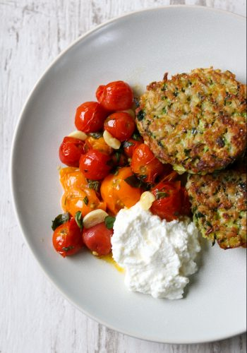 Zucchini barley cakes, roasted cherry tomatoes and ricotta cheese on a a plate