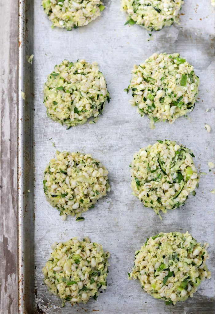 Uncooked zucchini barley cakes on a sheet pan