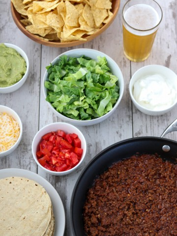 Taco ingredients in bowls with a beer on a wooden surface