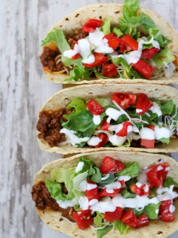 Three tacos with toppings on a wooden surface