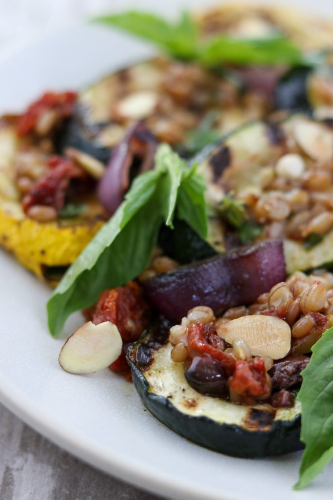 A close up of grilled summer squash salad with basil leaves