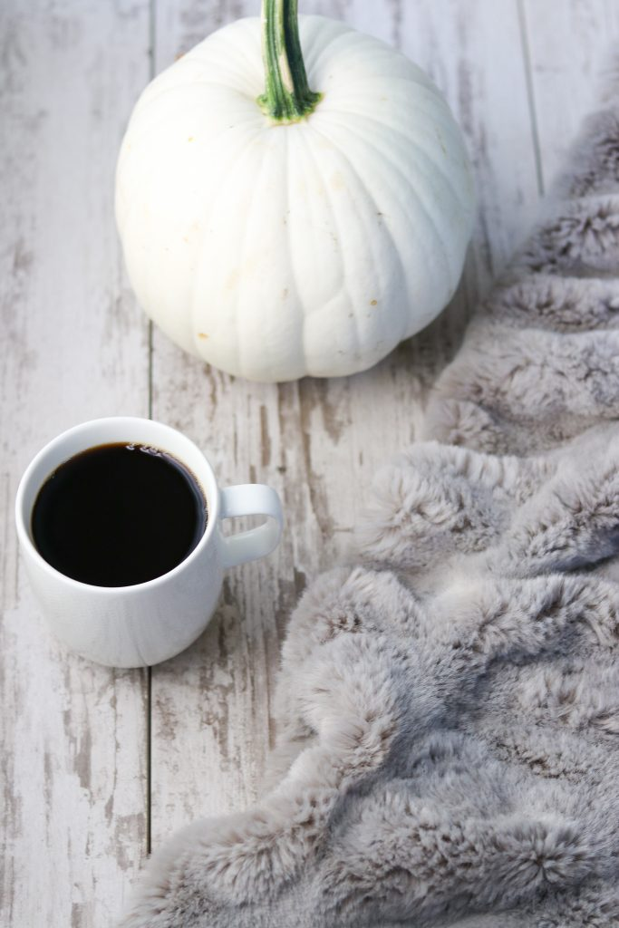 A blanket, pumpkin and a cup of coffee