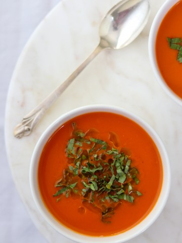 A bowl of tomato and red pepper soup topped with chopped basil and next to a spoon