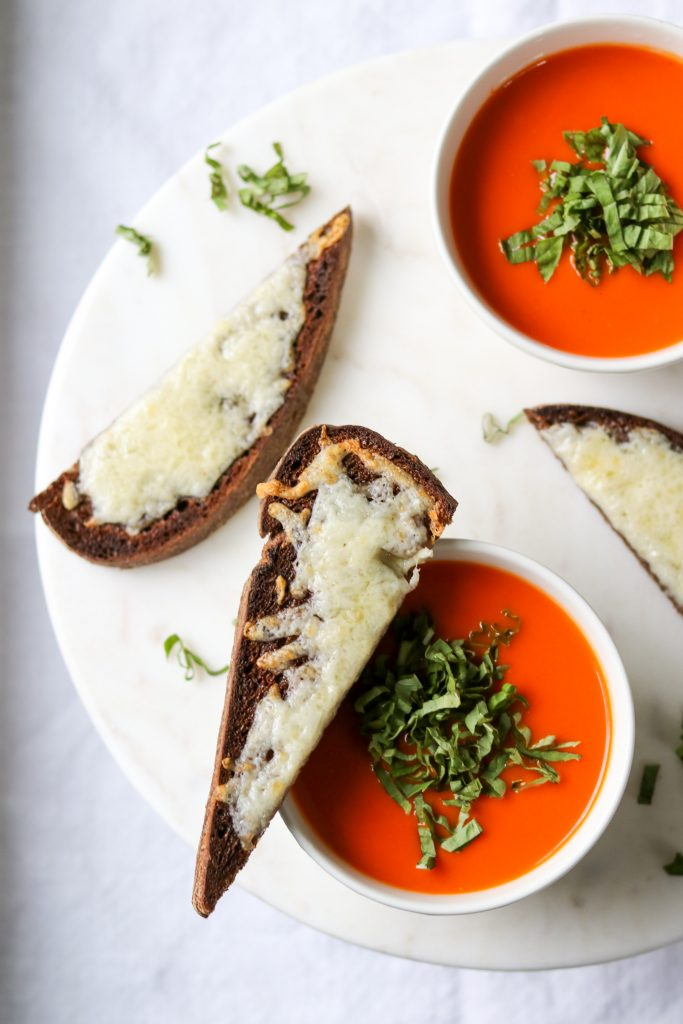 Bowls of tomato and red pepper soup with cheese-covered rye toasts